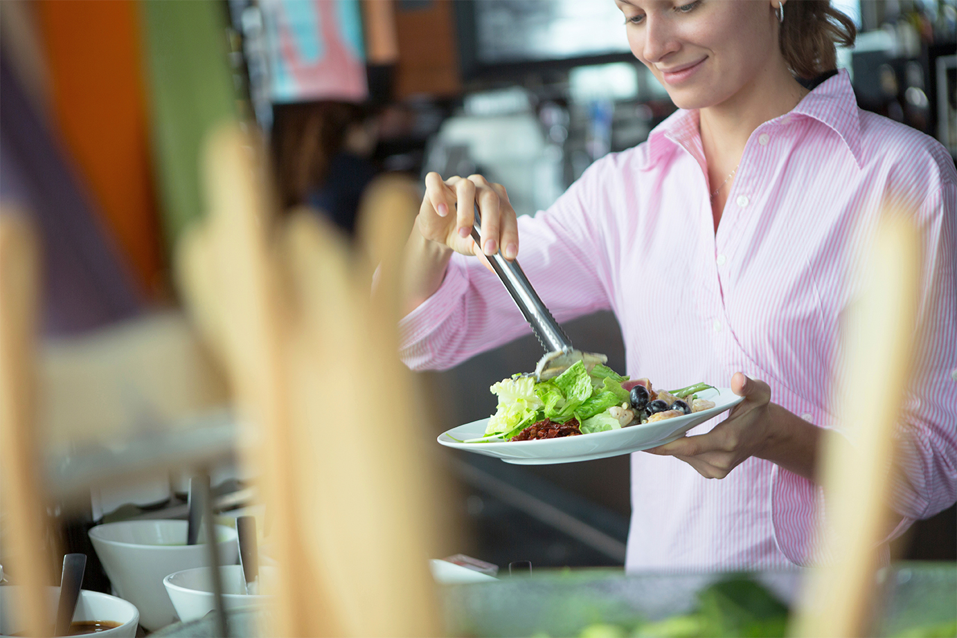 A woman puts salad on her plate while smiling
