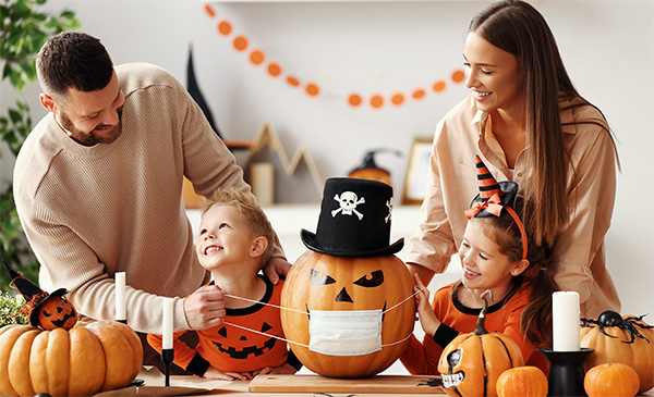 A mom, dad, and their two children put a face mask on a pumpkin