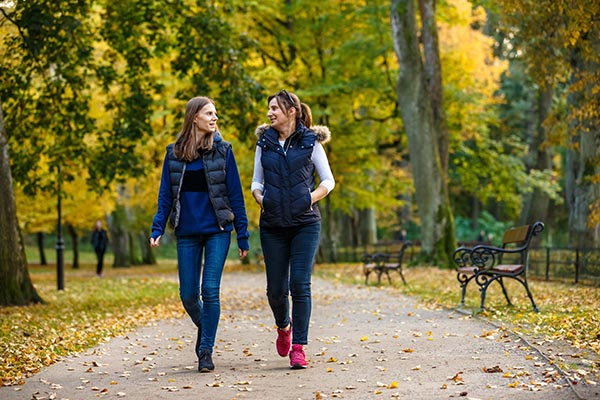 Two women look at each other while walking outdoors
