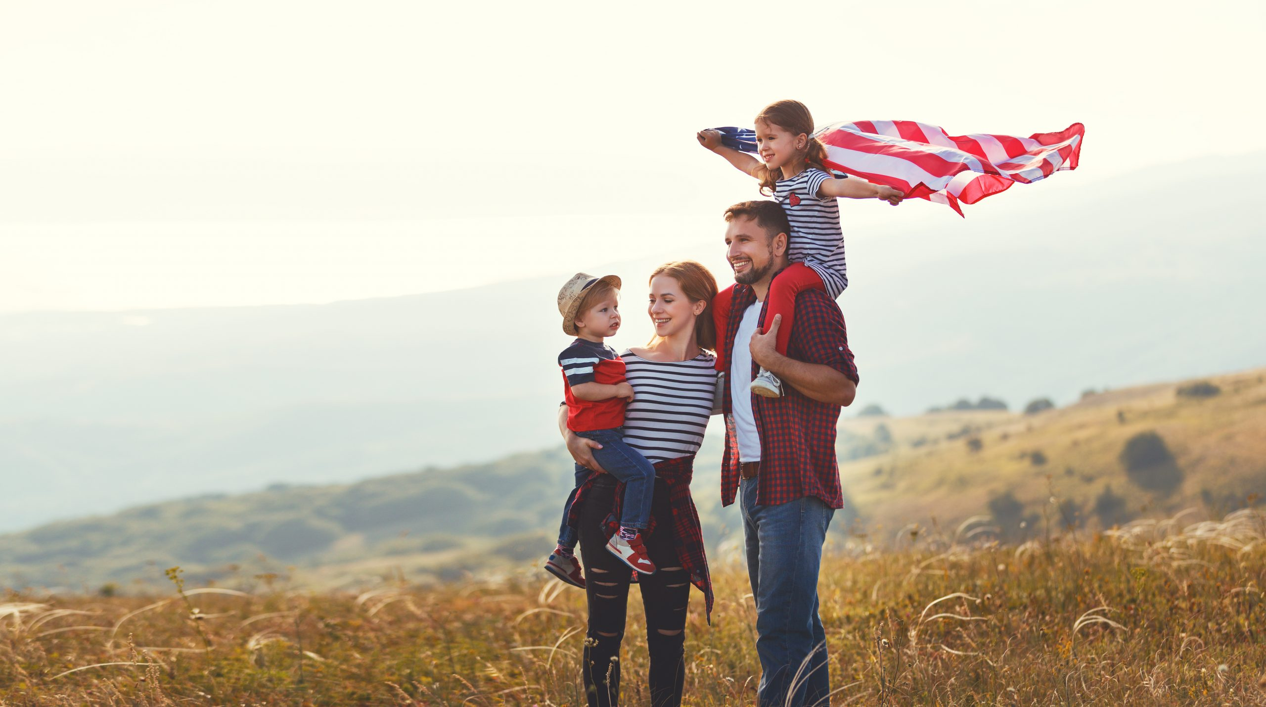 A family stands outside with an American flag